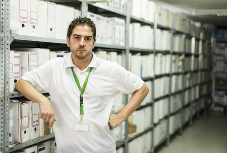 Portrait of serious looking man in an archive LANG_EVOIMAGES