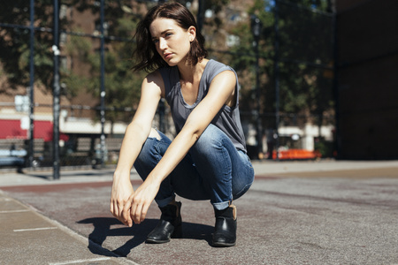 cowering: USA, New York City, Manhattan, young woman crouching on a playground LANG_EVOIMAGES