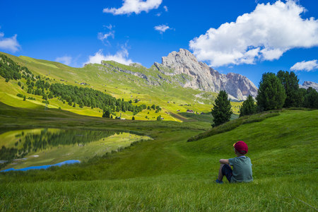 Italy, Dolomites, Odle range, Child resting in front of Seceda and lake Lech Sant LANG_EVOIMAGES