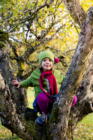 cowering: Portrait of smiling little girl sitting on tree trunk