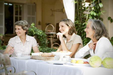 three generations: Spain, Mallorca, three female friends sitting at laid table in the garden