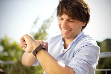 self testing: Smiling man outdoors looking at smartwatch