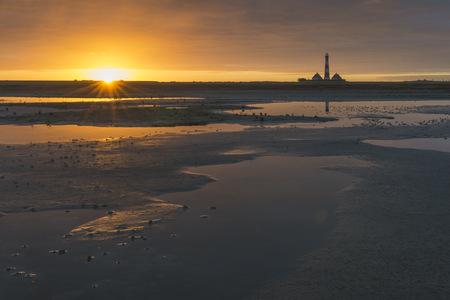 Germany, Schleswig-Holstein, North Sea Coast, View of Westerheversand Lighthouse, tideland at sunrise