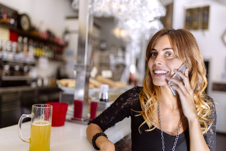 Portrait of smiling young woman telephoning with smartphone in a pub