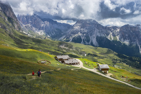 Italy, Dolomites, Odle mountain range, Hikers heading to a chalet