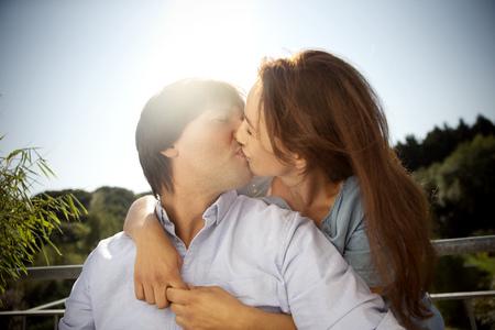 lighted: Couple kissing under blue sky LANG_EVOIMAGES