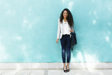 Portrait of smiling young businesswoman with leather bag standing in front of a blue wall LANG_EVOIMAGES