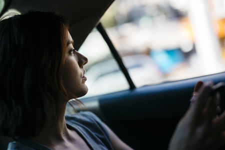 Profile of young woman sitting inside of a cab