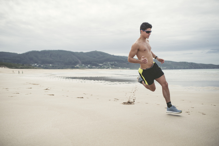 Spain, Ferrol, young man running fast on the beach LANG_EVOIMAGES