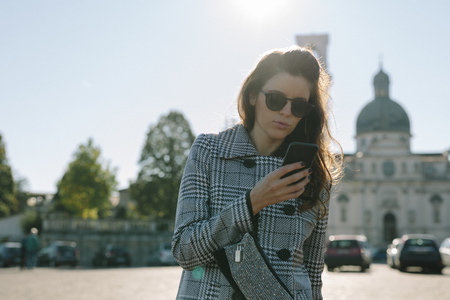 lighted: Italy, Vicenza, woman wearing checkered coat and sunglasses looking at cell phone