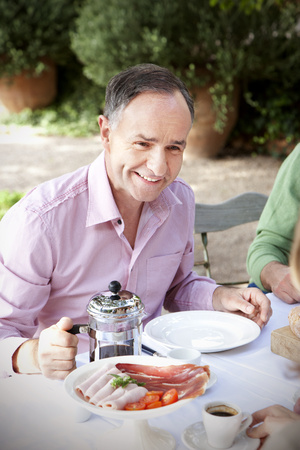 Portrait of smiling man sitting at laid table in the garden communicating with friends