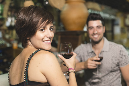 Smiling couple at bar drinking red wine