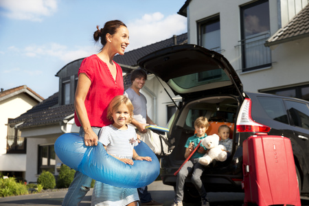 Happy family with floating tyre in driveway
