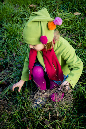 cowering: Little girl playing on a meadow in autumn LANG_EVOIMAGES