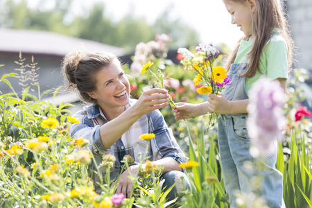 Happy mother and daughter picking flowers LANG_EVOIMAGES