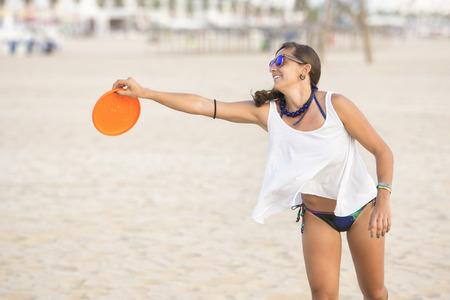 Spain, Cadiz, El Puerto de Santa Maria, Woman playing frisbee on the beach LANG_EVOIMAGES