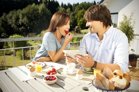 Happy couple having breakfast on balcony