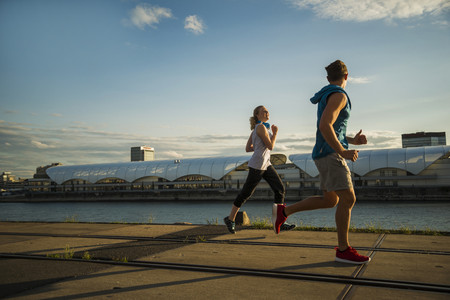 Young couple running by the riverside LANG_EVOIMAGES
