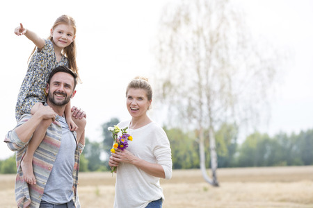 Family of three in field with father carrying daughter on shoulders LANG_EVOIMAGES