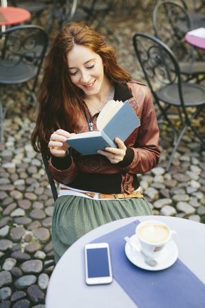Woman reading a book outdoors in a little bar