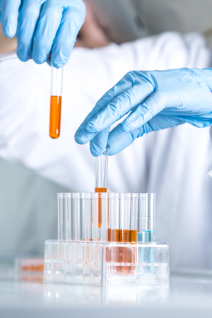 Scientist in lab working with test tubes