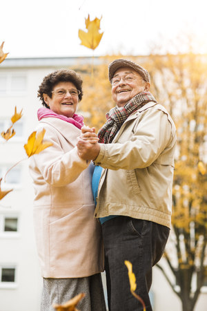 Happy senior couple dancing outdoors in autumn LANG_EVOIMAGES