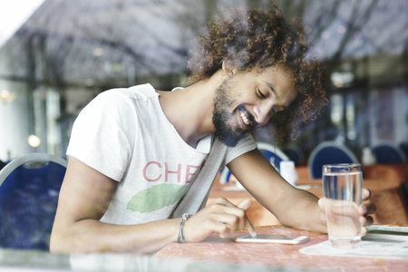 Portrait of smiling man sitting in a cafe using smartphone