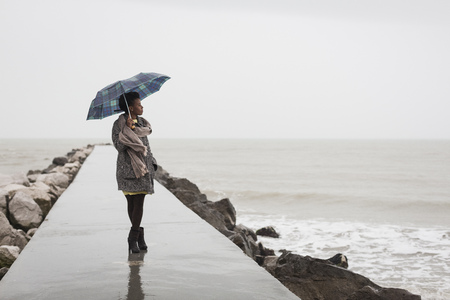 Italy, Grado, woman with umbrella on a rainy day looking at the sea