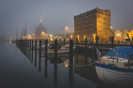 Germany, Eckernfoerde, harbor with old warehouse in fog LANG_EVOIMAGES