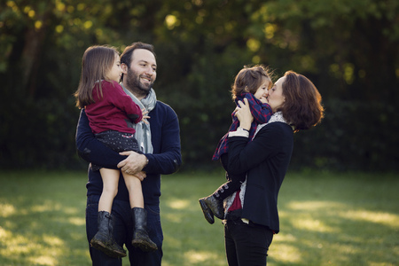 Parents with their little daughters in a parc