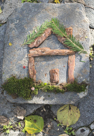 Pieces of fir branch, lichen and bark building shape of a house LANG_EVOIMAGES