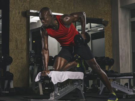 motivations: Physical athlete exercising with dumbbell in gym LANG_EVOIMAGES