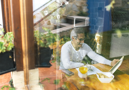 Man behind windowpane sitting at breakfast table reading a book