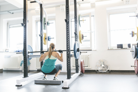 motivations: Woman doing barbell squats in a power rack LANG_EVOIMAGES