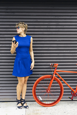 Woman with smartphone and red racing cycle waiting in font of roller shutter