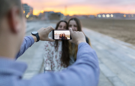 lighted: Man taking a selfie of his friends at evening twilight LANG_EVOIMAGES