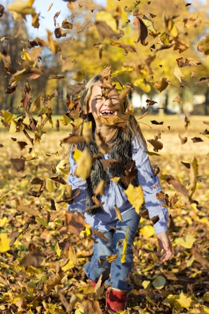 ardor: Laughing little girl throwing autumn leaves in the air