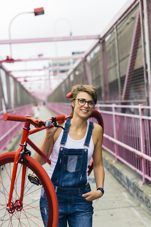 dungarees: USA, New York City, Williamsburg, woman carrying red racing cycle on her shoulder on Williamsburg Bridge LANG_EVOIMAGES