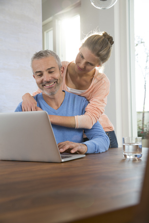 lighted: Couple at home working from laptop