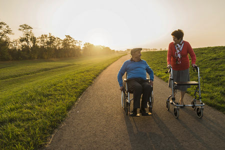 Smiling senior couple with wheelchair and wheeled walker on a path LANG_EVOIMAGES