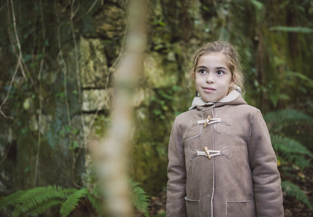 Portrait o little girl standing in the forest in autumn