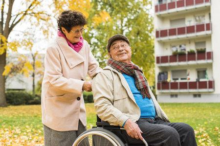 Senior woman pushing husband in wheelchair LANG_EVOIMAGES