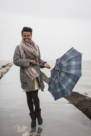 scarves: Italy, Grado, woman holding umbrella on a rainy day in front of the sea