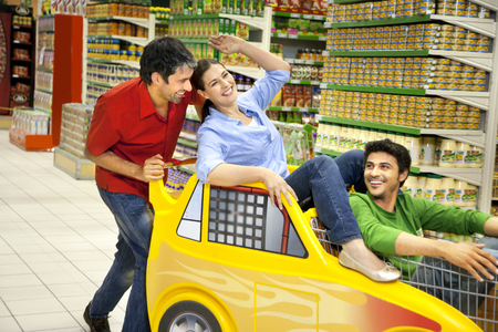 Three friends having fun together in a supermarket LANG_EVOIMAGES