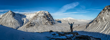 UK, Scotland, Glencoe, Glen Etive, woman cheering in winter landscape LANG_EVOIMAGES