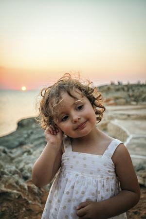 Spain, Menorca, portrait of smiling little girl at sunset