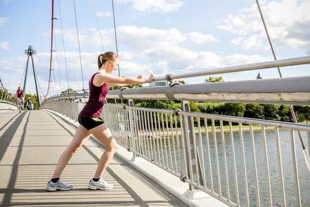 motivations: Germany, Frankfurt, young athlete stretching on bridge