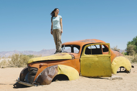 Namibia, Namib desert, Woman standing on an abandoned car in Solitaire LANG_EVOIMAGES