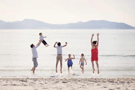 feet naked: France, La Ciotat, couple with four children jumping in the air at seafront