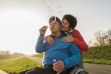 Senior woman with husband in wheelchair blowing soap bubbles